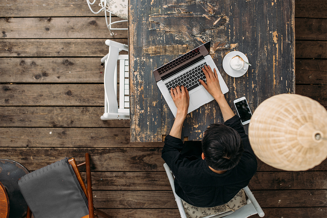 An overhead photo of a man using a laptop at a cafe